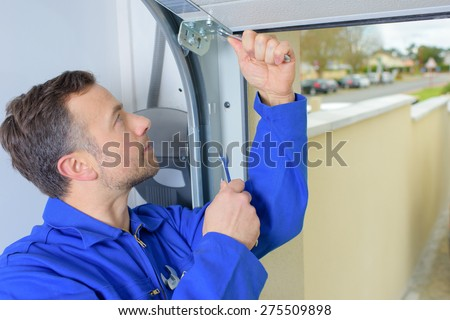 Man installing a garage door - stock photo