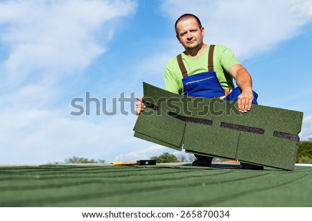 Man installing bitumen roof shingles - holding a few pieces - stock photo
