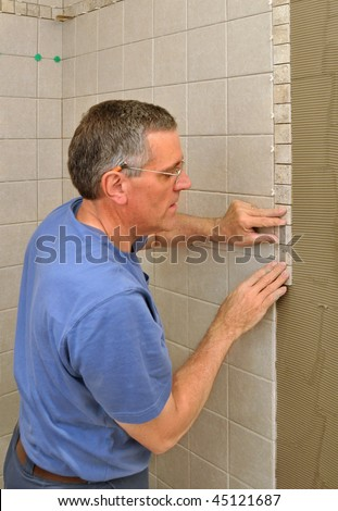 Man installing border of small ceramic tiles on bathroom wall in shower area - stock photo