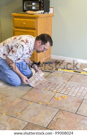 Man installing ceramic tile in customers kitchen, getting ready to sell home - stock photo