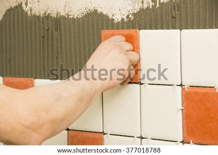 Man installing ceramic tile on a wall - stock photo