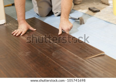 Man Installing New Laminate Wood Flooring Abstract. - stock photo
