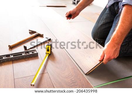 Man installing new laminated wooden floor - stock photo