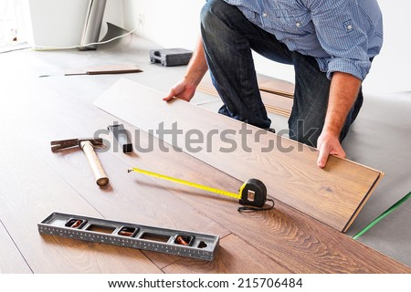 Man installing new laminated wooden floor - stock photo