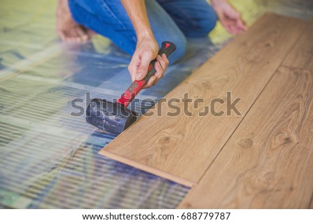 Man installing new wooden laminate flooring on a warm film floor  infrared floor  heating system. Heated Floors Stock Images  Royalty Free Images   Vectors