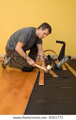 Man installing tongue and groove hardwood floor.