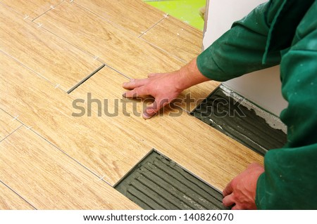 Man installs ceramic tile - stock photo