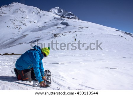 Man installs splitboard, in the background can be seen walking on top of the mountain freeriders