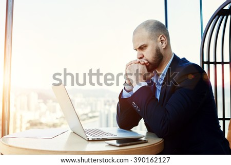 Man intelligent managing director is reading important e-mail letter on laptop computer, while is sitting in modern office interior. Worried economist is analyzing activities of  company via net-book
