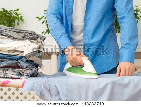 Man ironing clothes on ironing board at home. - stock photo