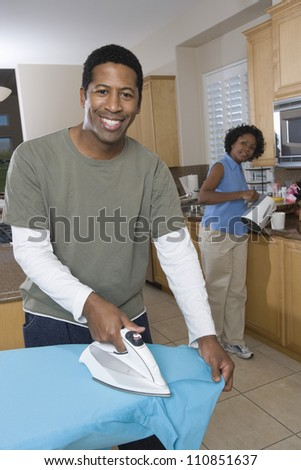 Man ironing his shirt in the kitchen