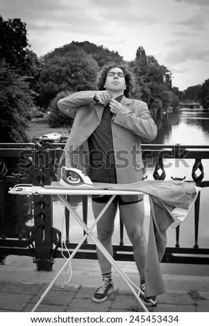 Man ironing his suit in the city, by a canal in Amsterdam - stock photo