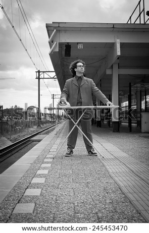 Man ironing his suit in the city on the platform of a train station - stock photo