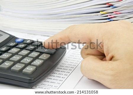 Man is accounting with calculator on the statement finance account.