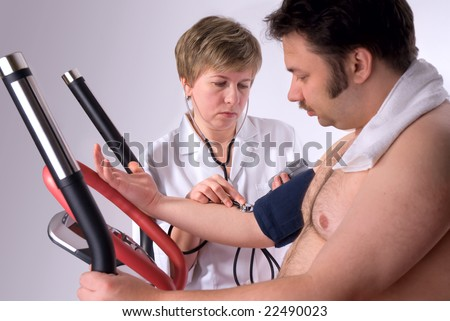 man is being observed by doctor after training, measuring blood pressure