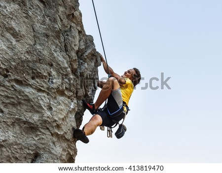 Man is climbing on the rock with harness and rope - stock photo