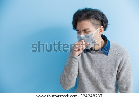 man is coughing isolated on blue background, asian
