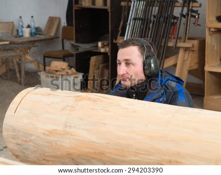 Man is cutting tree trunk with chainsaw. He is wearing soundproofing headsets - stock photo