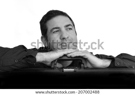 Man is day dreaming about travel while leaning on travel suitcase against white background with copy space. Concept photo of travel, vacation, holiday, destination, tourism, traveler, tourist.(BW) - stock photo