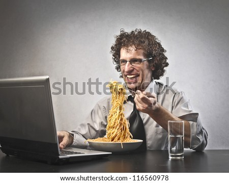 Man is eating red spaghetti while he is using a laptop computer - stock photo