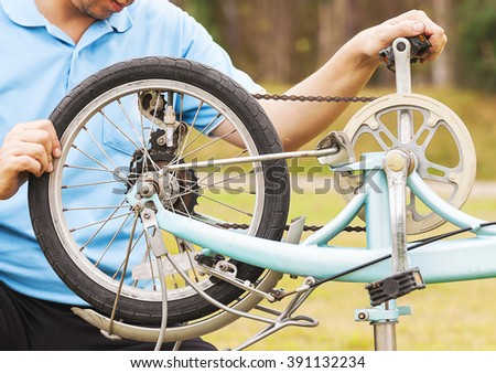 Man is fixing bicycle. Photo is focused at a wheel. - stock photo