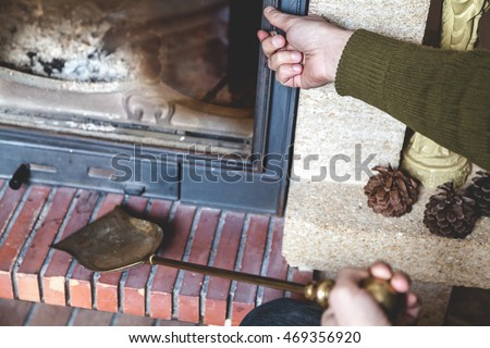 Man is going to clean the fireplace. Open the door and keep the blade