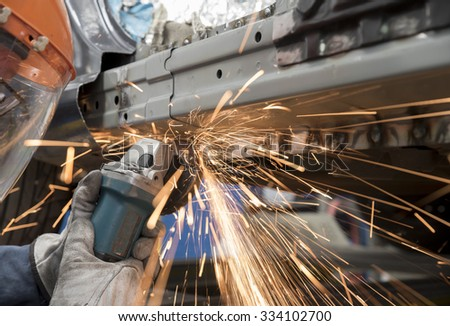 Man is grinding on the sill after welding the piece in place on a car. - stock photo