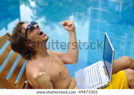 Man is happy and sits poolside with his laptop - stock photo