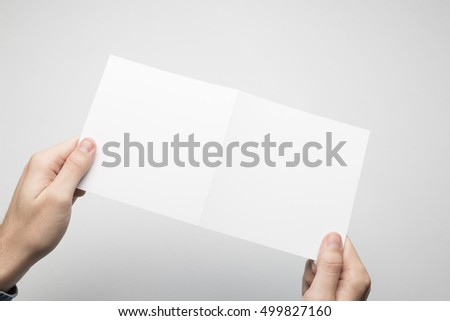 Man is holding a square Bi-Fold white paper flyer.