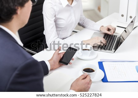 Man is holding a white coffee cup and looking at his cell phone. His coworker is typing in the background