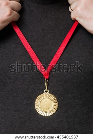 Man is holding and putting on golden medal on chest.