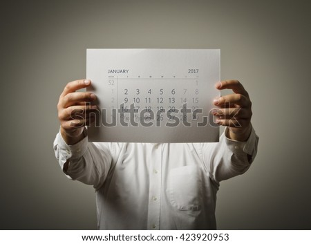 Man is holding January calendar of the year two thousand seventeen.