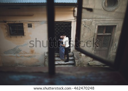 Man is kissing his woman next to the door