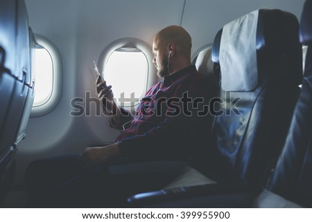 Man is listening audio training in headphones via mobile phone and looking at beautiful view outside the window. Male is enjoying his favorite music via cell telephone, while is flying in an airplane - stock photo