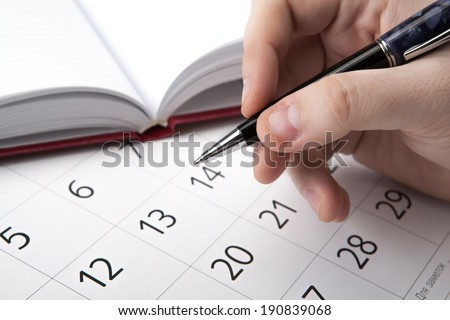 man is looking for information in the directory and calendar close-up - stock photo