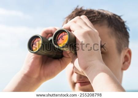man is looking to the binocular. Focus on the near binocular - stock photo