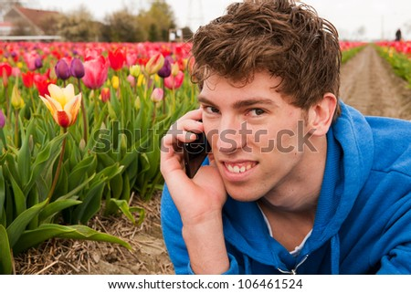Man is making a positive phone call in the flower fields - stock photo