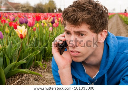 Man is making a sad phone call in the flower fields - stock photo