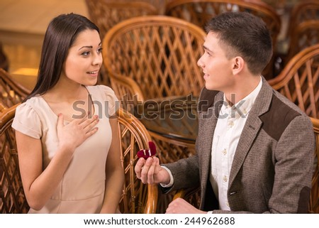 Man is making proposal with the ring to his girlfriend at the restaurant. Shocked and surprised woman. - stock photo