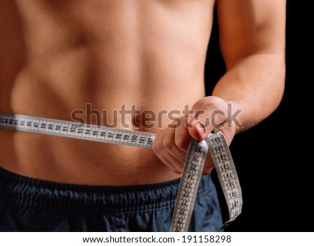 Man is measuring waist with centimeter tape, face is not visible - stock photo