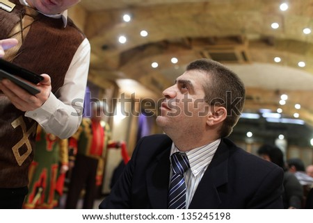 Man is ordering food in an armenian restaurant - stock photo