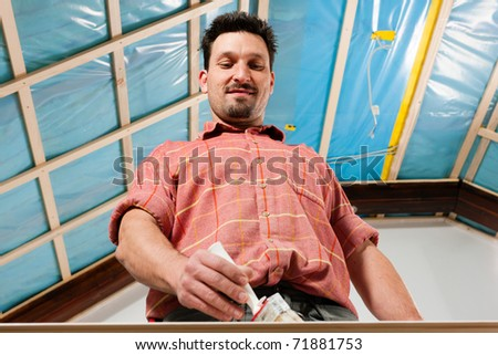 Man is painting in his house; presumably he is renovating - stock photo