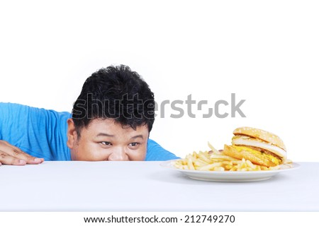 Man is peeping hamburger on the table, isolated on white background - stock photo