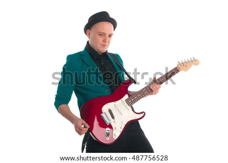 Man is posing with the electric guitar wearing a hat and jacket.