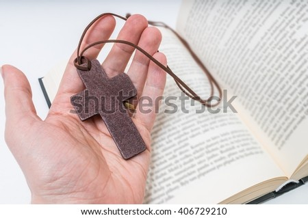 Man is praying. Prayer's hand holds crucifix. Bible in background. - stock photo