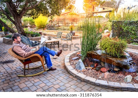 Man is reading a newspaper on a patio in a cozy garden - stock photo
