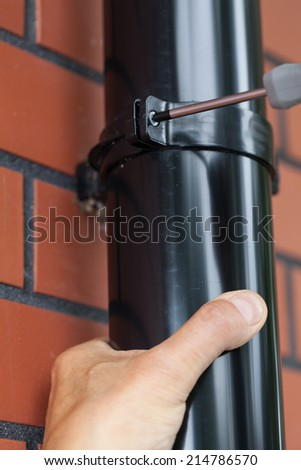 Man is repairing a gutter in the garden - stock photo