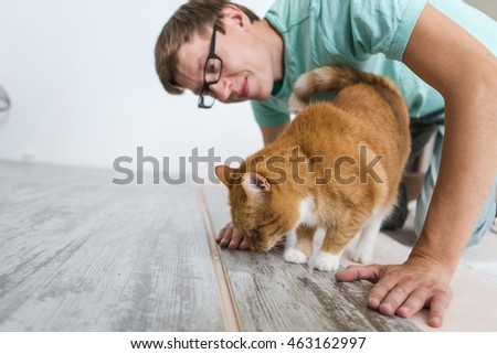 man is repairing the floor in the house, laminate flooring in the style of old boards. Red cat, pet.