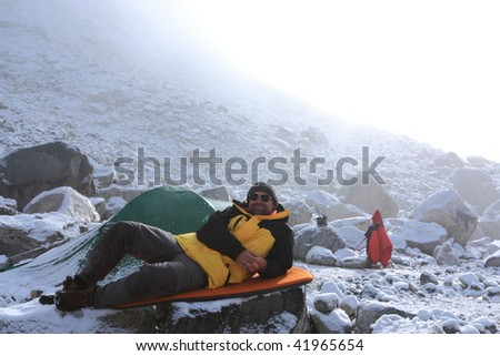 Man is resting in the mountaineering camp in misty morning