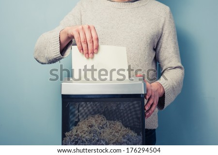 Man is shredding a piece of paper - stock photo